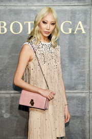 Soo Joo Park attended the Bottega Veneta fashion show carrying a stylish pink crocodile bag with a gold chain strap.