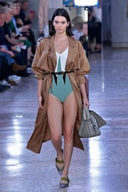 Kendall Jenner walked the Bottega Veneta show wearing a tan trenchcoat over a one-piece swimsuit.