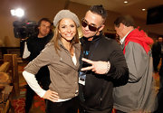 Mike wears a black zip-up track jacket while posing with Maria Menounos at the Super Bowl half time show.