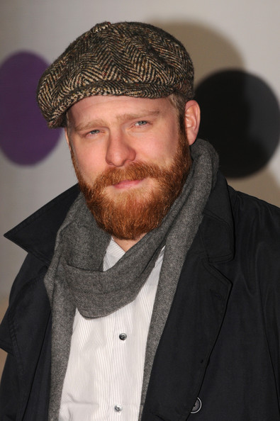Alex Clare donned a tweed newsboy cap for a more casual red carpet look at the 2013 Brit Awards.