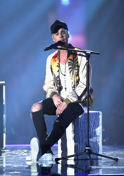 Justin Bieber performed at the 2016 Brit Awards wearing a tropical-print bomber jacket by Saint Laurent.