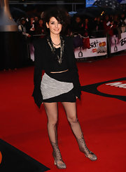 Katie Melua stroke a pose for the cameras at the Brit Awards. She donned an unique pair of lace-up ankle boots which probably weren't the best match to her mis-matched ensemble.