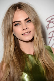 Oh-so-subtle waves and a sleek center part put all the emphasis on Cara's signature bold brows.