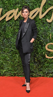 Victoria Beckham went for menswear-inspired elegance in a black satin-trimmed tux by Burberry at the British Fashion Awards.