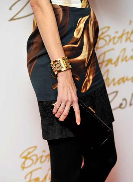 Claudia Schiffer looked stunning carrying a simple yet chic black patent clutch with a gold closure.
