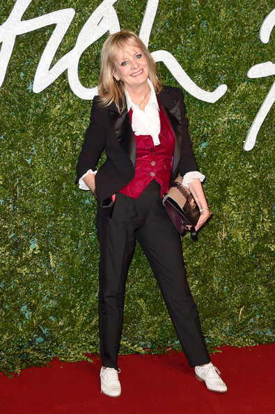Twiggy made an appearance at the British Fashion Awards wearing a black tuxedo over a red vest and a white ruffle blouse.
