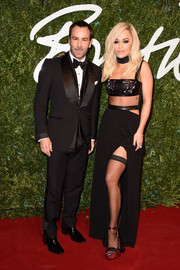 Rita Ora was edgy-sexy on the British Fashion Awards red carpet in a black Tom Ford gown featuring waist cutouts, a thigh-high slit, and a bejeweled leather bandeau top.