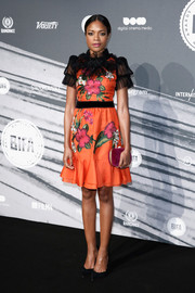 Naomi Harris accessorized with a magenta velvet clutch by Gucci that matched the flower embroidery on her dress.