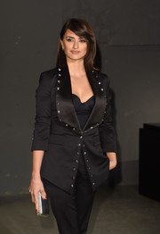 Penelope Cruz paired a metallic silver clutch with a black pantsuit for the Burberry fashion show.