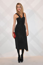 Beauty Cara Delevingne added a burst of color to her black halter dress with a red zip around clutch.