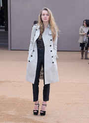 Immy Waterhouse arrived for the Burberry fashion show wearing a trenchcoat over a lacy top and slacks.