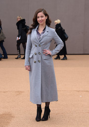 Raya Abirached kept warm with a gray wool coat while attending the Burberry fashion show.