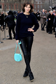 Alexa Chung added a pop of color to her all black attire with a robins egg blue patent leather crossbody bag.