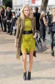Donna paired her lime green cocktail dress with ankle boots and a metallic tote bag.