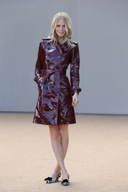 Poppy Delevingne paid homage to Burberry by wearing the brand's metal plate rubber trench coat during London Fashion Week.
