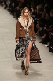 Suki Waterhouse walked down the Burberry runway wearing a stylish fur-lined suede jacket over a print dress.
