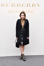 Riley Keough was military-chic in a black Burberry trenchcoat while attending the label's fashion show.