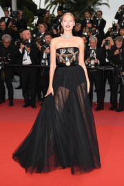 Toni Garrn struck a pose on the Cannes red carpet wearing a strapless black Elie Saab gown with an embellished bodice and a sheer skirt.