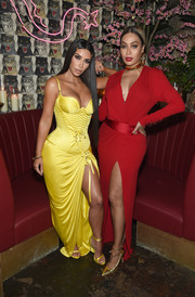 La La Anthony flaunted her cleavage and leg in a deep-V red wrap gown at the Business of Fashion dinner.
