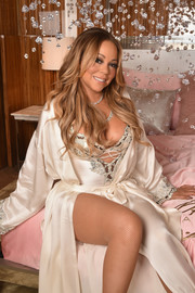 Mariah Carey struck a sexy pose in a lace-trimmed bodysuit and a matching robe during the launch of her M.A.C. Cosmetics Beauty Icon collection.