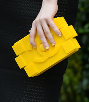 Bella Heathcote rocked a bright yellow hard case clutch at the Chanel Dinner for the NRDC.