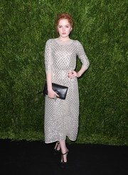 Ellie Bamber looked effortlessly stylish at the Chanel dinner in honor of Keira Knightley wearing this gray sweater dress with metallic lattice embellishments.