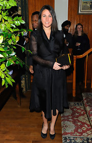 Katherine dons a black wrap dress made of crisp fabric for the Chanel dinner party.