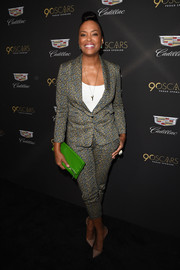 Aisha Tyler styled her suit with a bright green patent clutch.