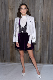 Millie Bobby Brown topped off her look with a white leather biker jacket by Calvin Klein.