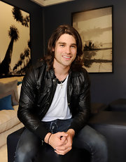 Justin Gaston keeps his wavy hair shoulder length and layered.