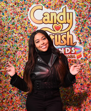 Jordyn Woods layered a cropped black leather jacket over a matching turtleneck for the Candy Crush Friends Sweet n Solo event.