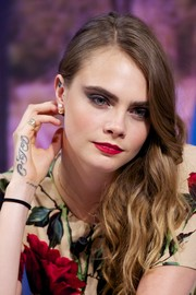 Cara Delevingne kept the feminine vibe going with a bold red lip.
