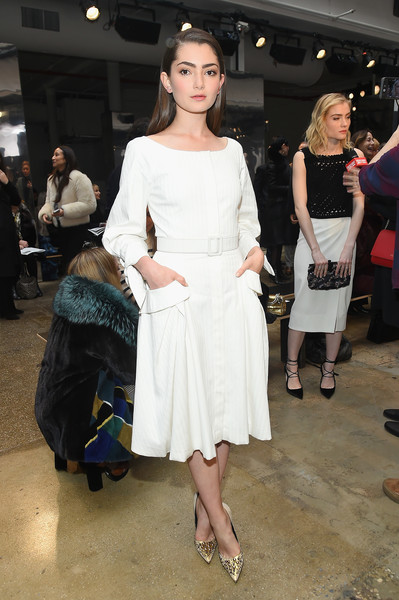 Emily Robinson looked very prim and proper in a long-sleeve white midi dress by Carolina Herrera while attending the label's fashion show.