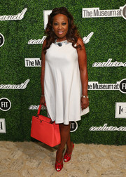 Star Jones accessorized with a bright red Louis Vuitton leather tote for a splash of color to her white dress.