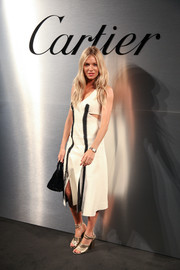 Sienna Miller styled her dress with gold ankle-strap sandals by Alumnae.