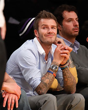 The charming David Beckham showed off loads of tattoos along with a silver chronograph watch featuring a black face.