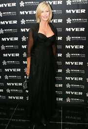 Olivia Newton-John donned a mature black evening gown with chiffon sleeves to the Precious Metal Ball.