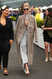 Rachael Taylor was spotted out on Caulfield Cup Day wearing a striped tan coat over a gray dress.