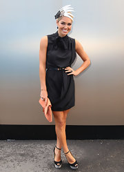 Ashley Hart added a contrast to her all-black ensemble by carrying an orange envelope clutch.