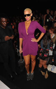 Amber showed off her womanly curves in a plunging purple dress. She topped off her look with bold black shades.