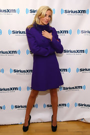 Camille Grammer posed in a bright purple double-breasted coat and towering pumps.