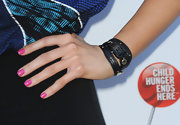 Stephanie wore a black wrapped strap wrist watch with gold hardware. The trendy accessory looked awesome with her pretty pink manicure.