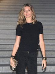 Gisele Bundchen styled her casual outfit with thick gold cuffs on both wrists when she attended the Chanel Cruise show.