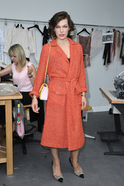 Milla Jovovich looked tres chic in a slouchy orange tweed coat by Chanel while attending the label's Couture show.