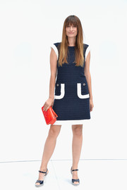 Caroline De Maigret's red Chanel patent leather purse provided a stylish color contrast to her navy dress.