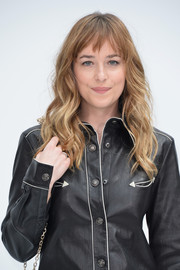 Dakota Johnson wore her hair down with beachy waves and jagged bangs during the Chanel Couture fashion show.