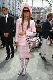 Staying true to the runway styling, Anna dello Russo teamed her suit with matching pink Chanel lace-up boots.