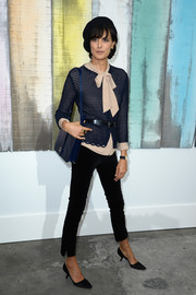Ines de la Fressange teamed black cigarette pants with a tie-neck blouse and a cardigan for the Chanel fashion show.