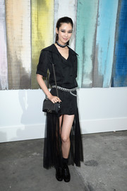 Tao Okamoto went for a goth vibe in a black fishtail dress, boots, and smoky eye makeup during the Chanel fashion show.