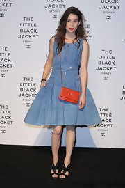 Astrid Berges-Frisbey incorporated a classic orange Chanel clutch with her denim look at the Little Black Jacket Exhibition Launch.